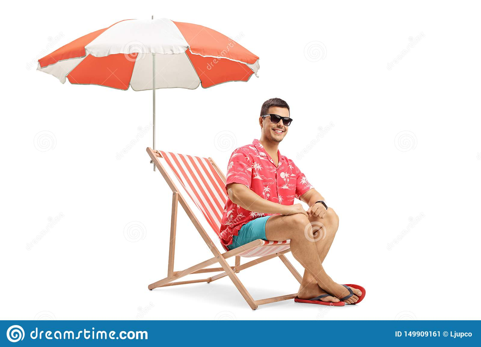 Young man sitting on a deckchair under an umbrella and smiling at the camera
