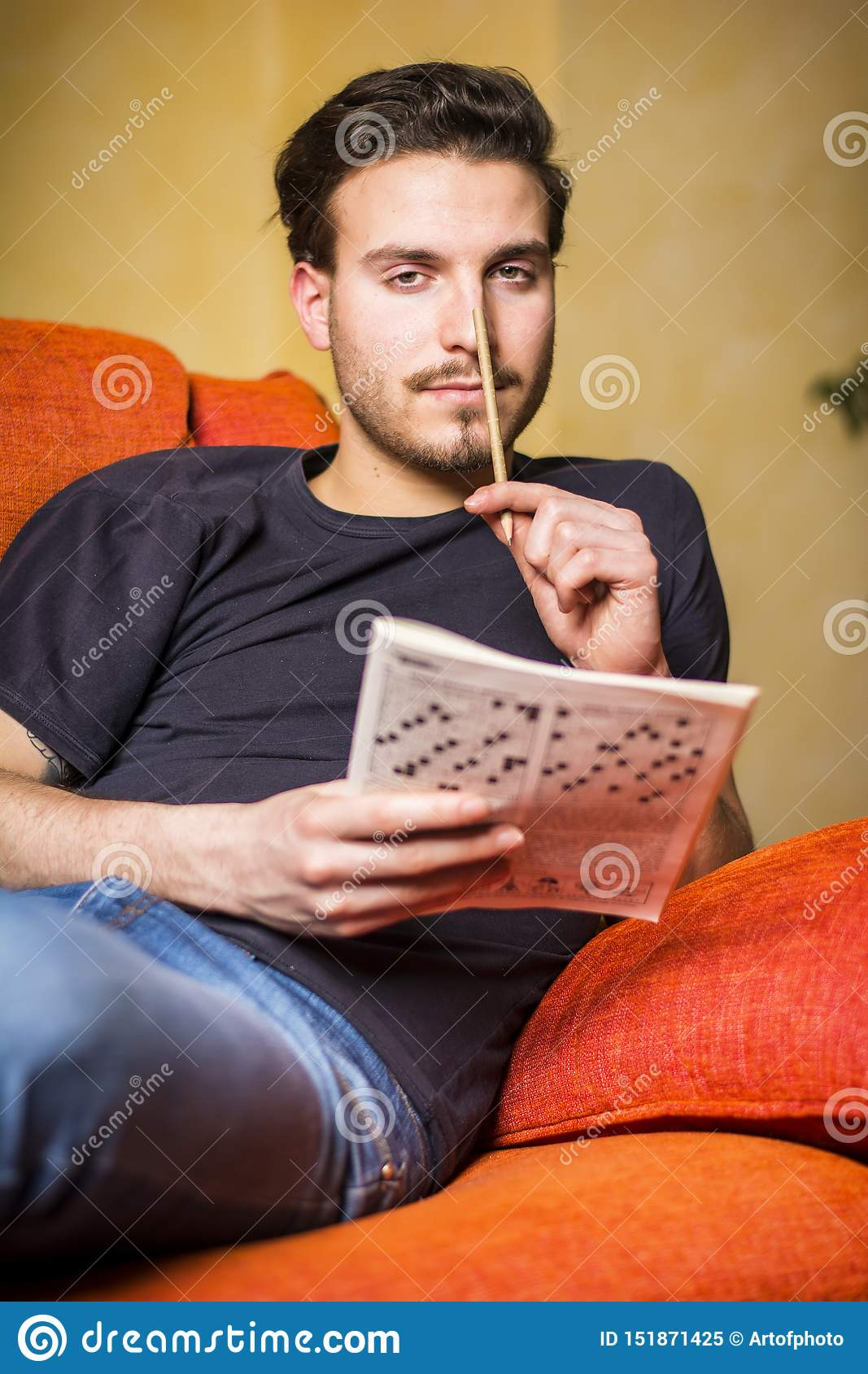 Young Man Sitting Doing A Crossword Puzzle Stock Image Image Of Living Amusement 151871425