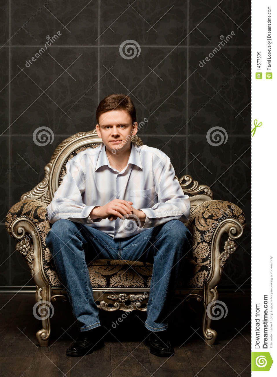 Young man sitting in magnificent ancient armchair royalty for Sitting in armchair