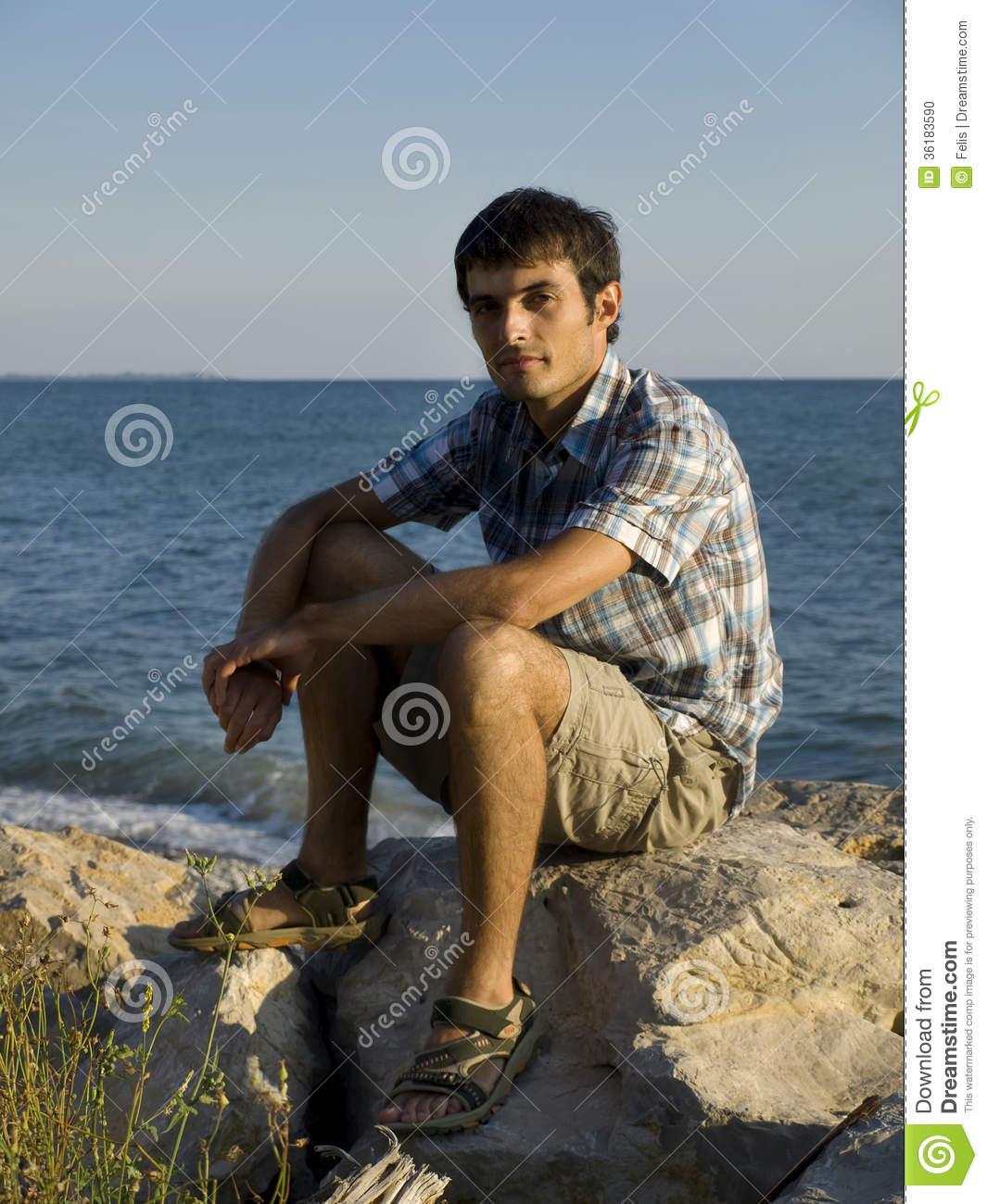 Young Man Sitting On Rocks Near Sea During Sunset Stock ...
