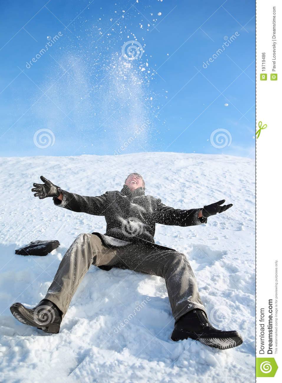 Young Man Sitting On Snow And Throw Him Upwards Stock