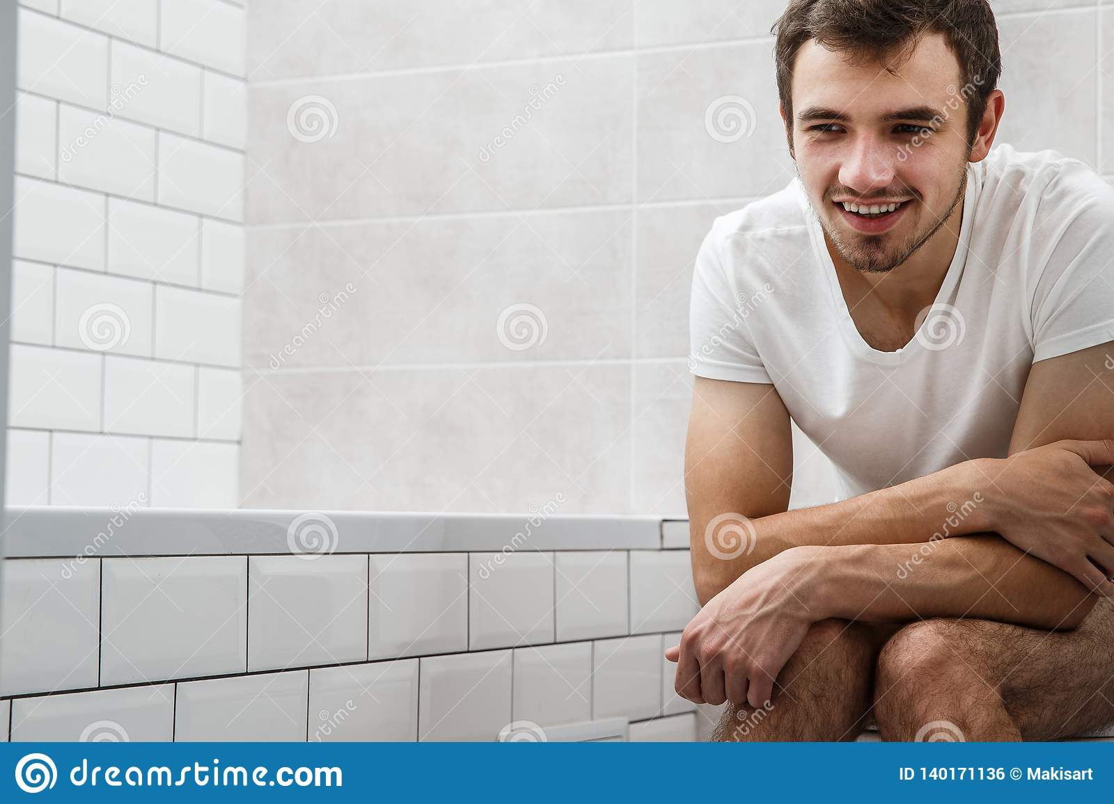 Young Businessman Working In Toilet With Laptop Stock