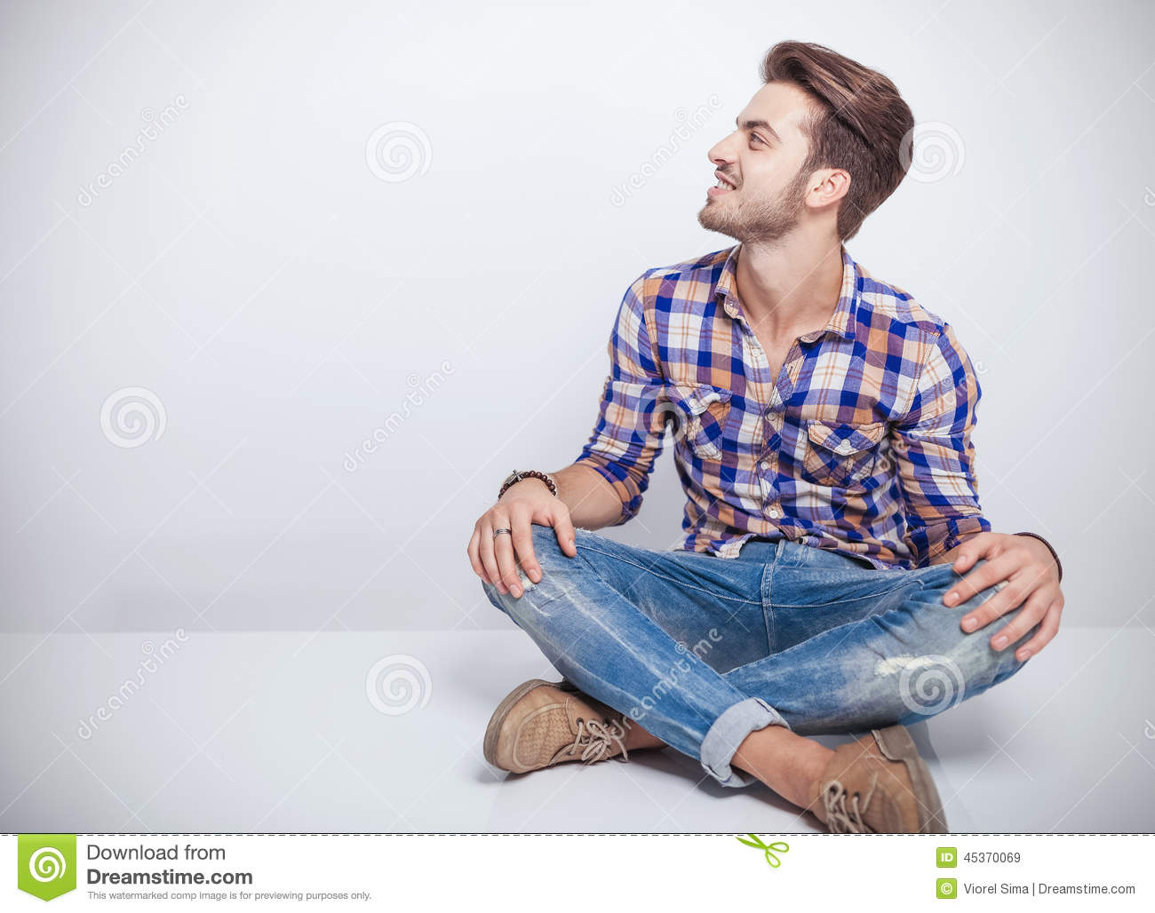 Young Man Sitting White Table His Legs Crosed Cool Looking Away Smiling Attractive Stylish Guy Model