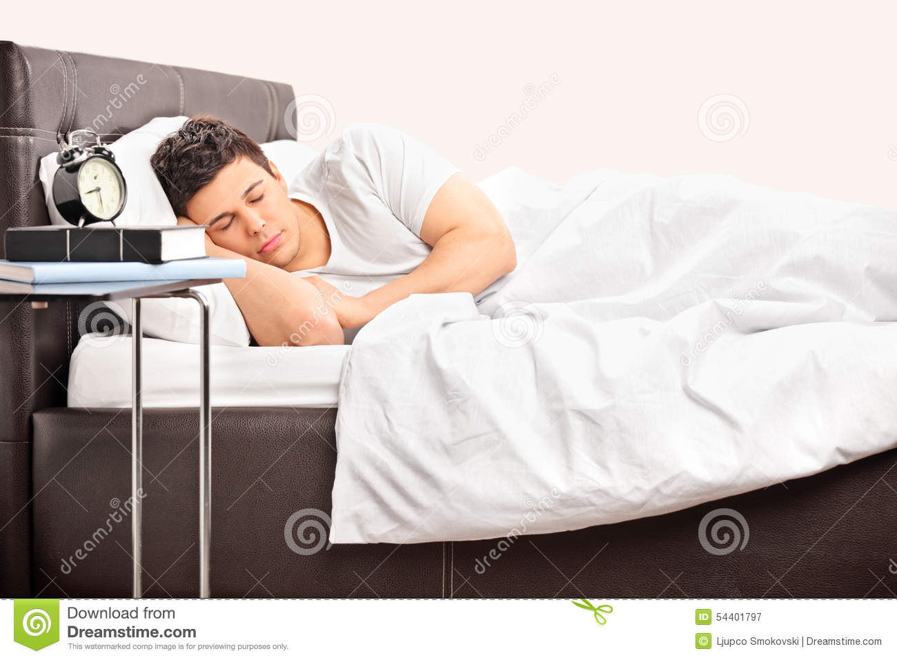 Young Man Sleeping On A Comfortable Bed Stock Photo