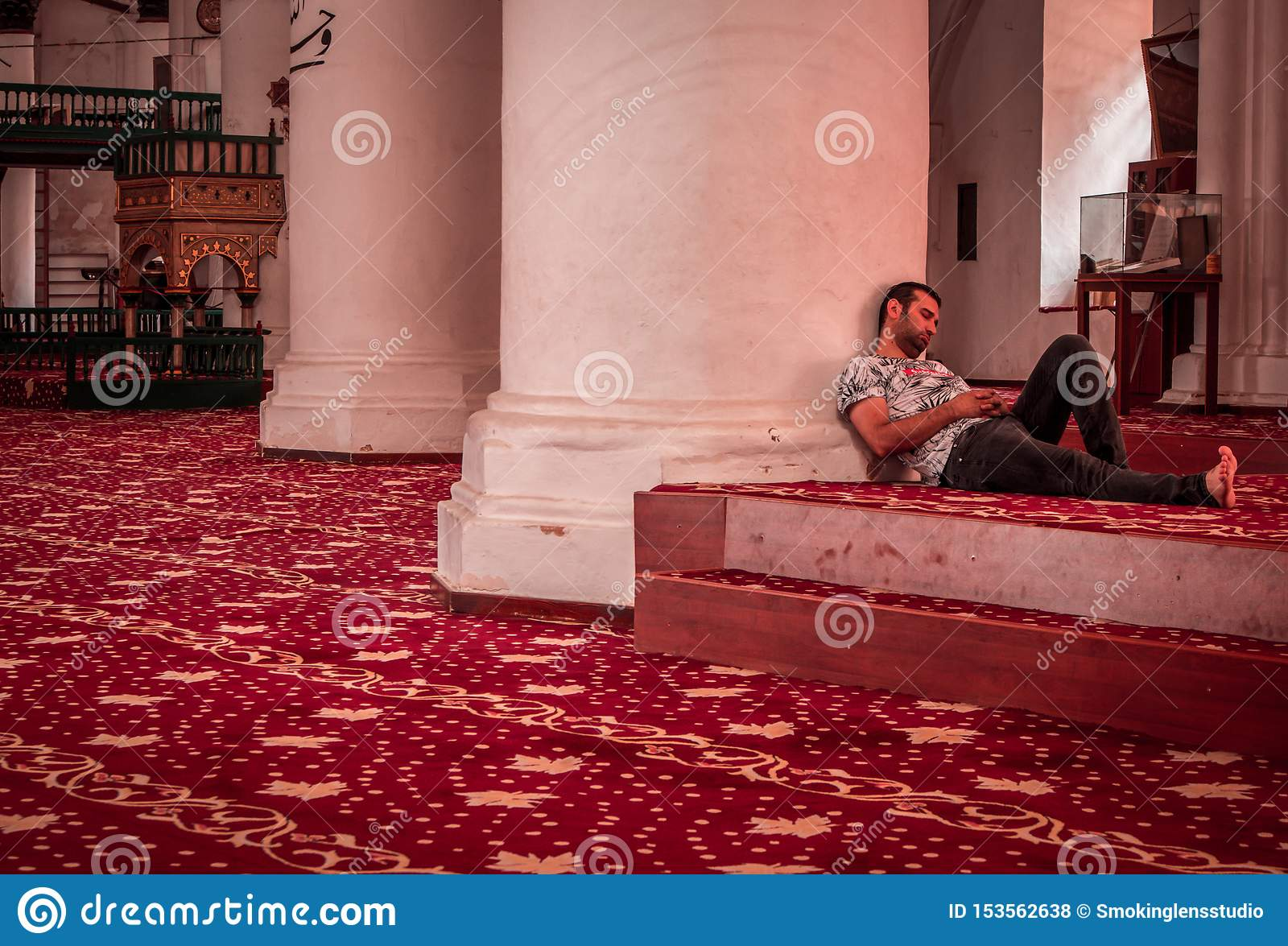 Man sleeping in a mosque, wearing casual