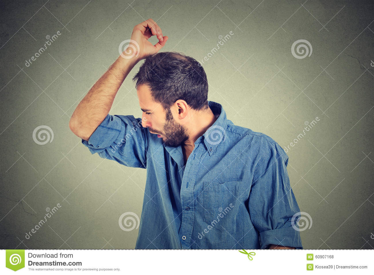 Young man, smelling, sniffing his armpit, something stinks