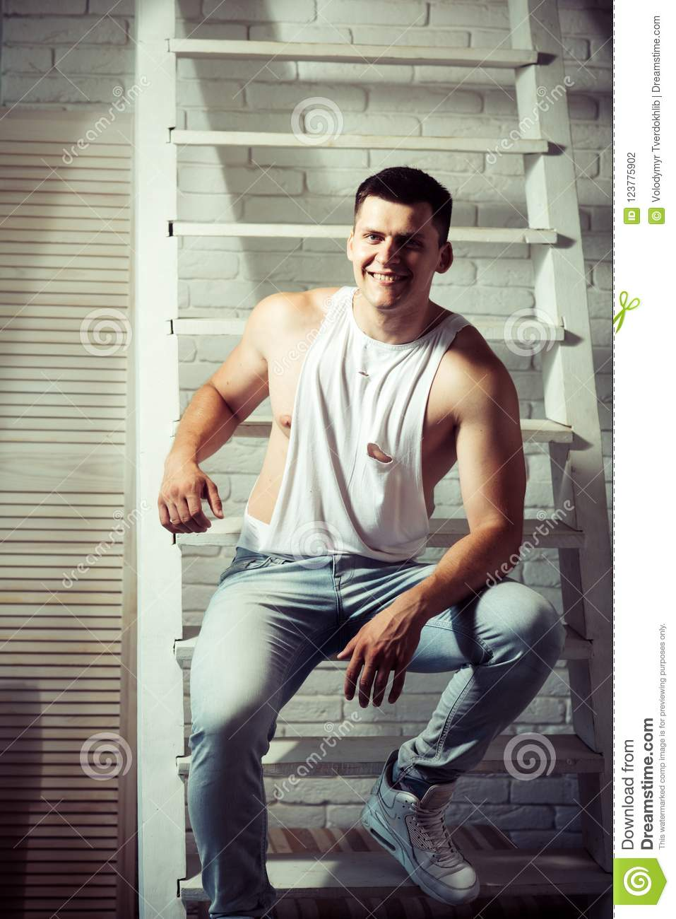 2fbac3c6b6447 Young man smile on ladder. Guy in trendy tank top and jeans fashion.  Athletic