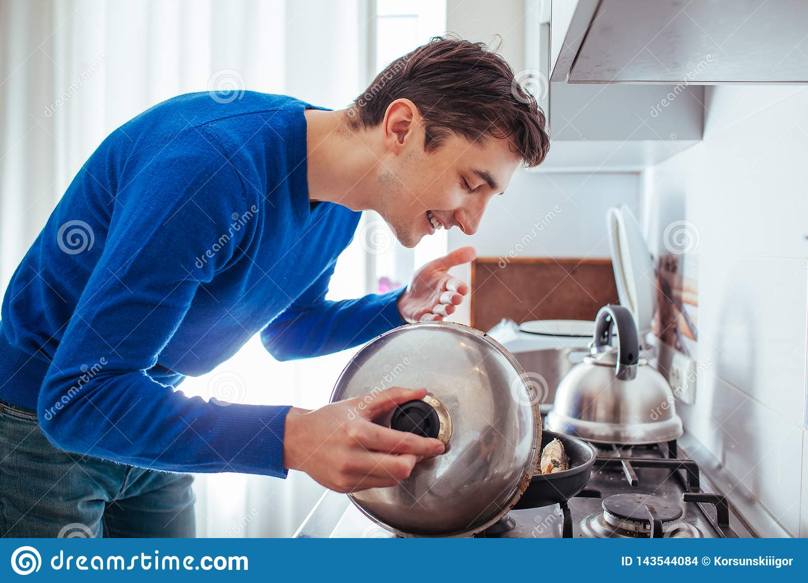 Young man sniffing food from the pan