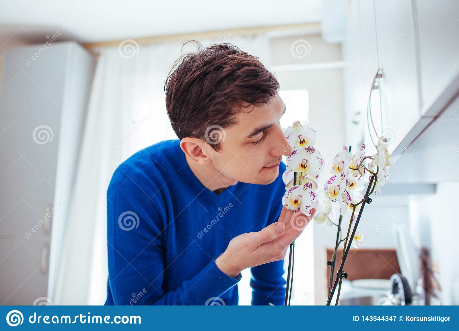 Young man sniffing orchid in kitchen at home