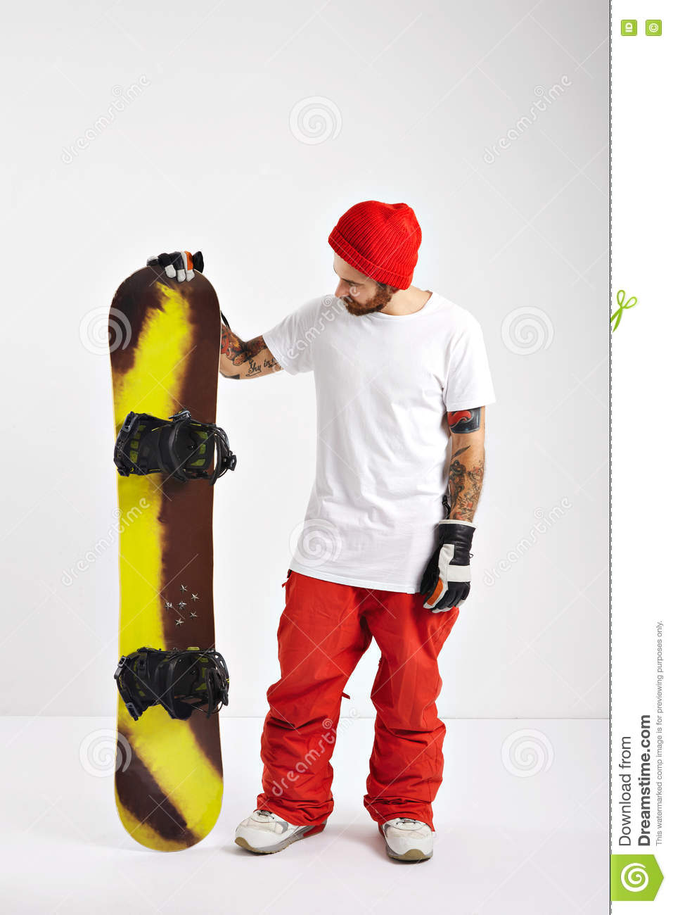 Young man with a snowboard in studio