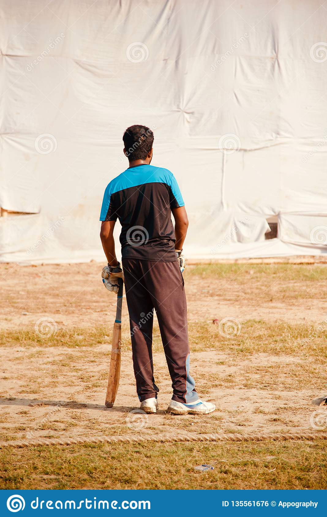 Young man standing in a field holding a bat