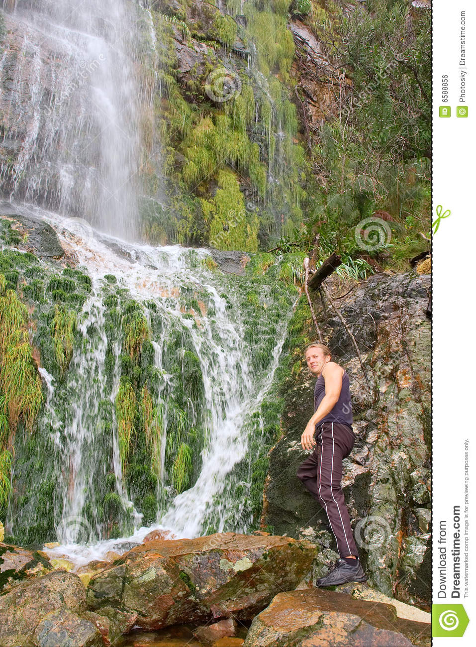 Young Man Standing Next To Waterfall Royalty Free Stock