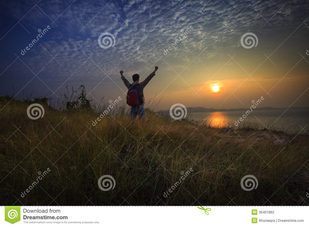 Young man standing and rising hand as victory on grass hill looking to sun above sea horizontal with dramatic colorful sky