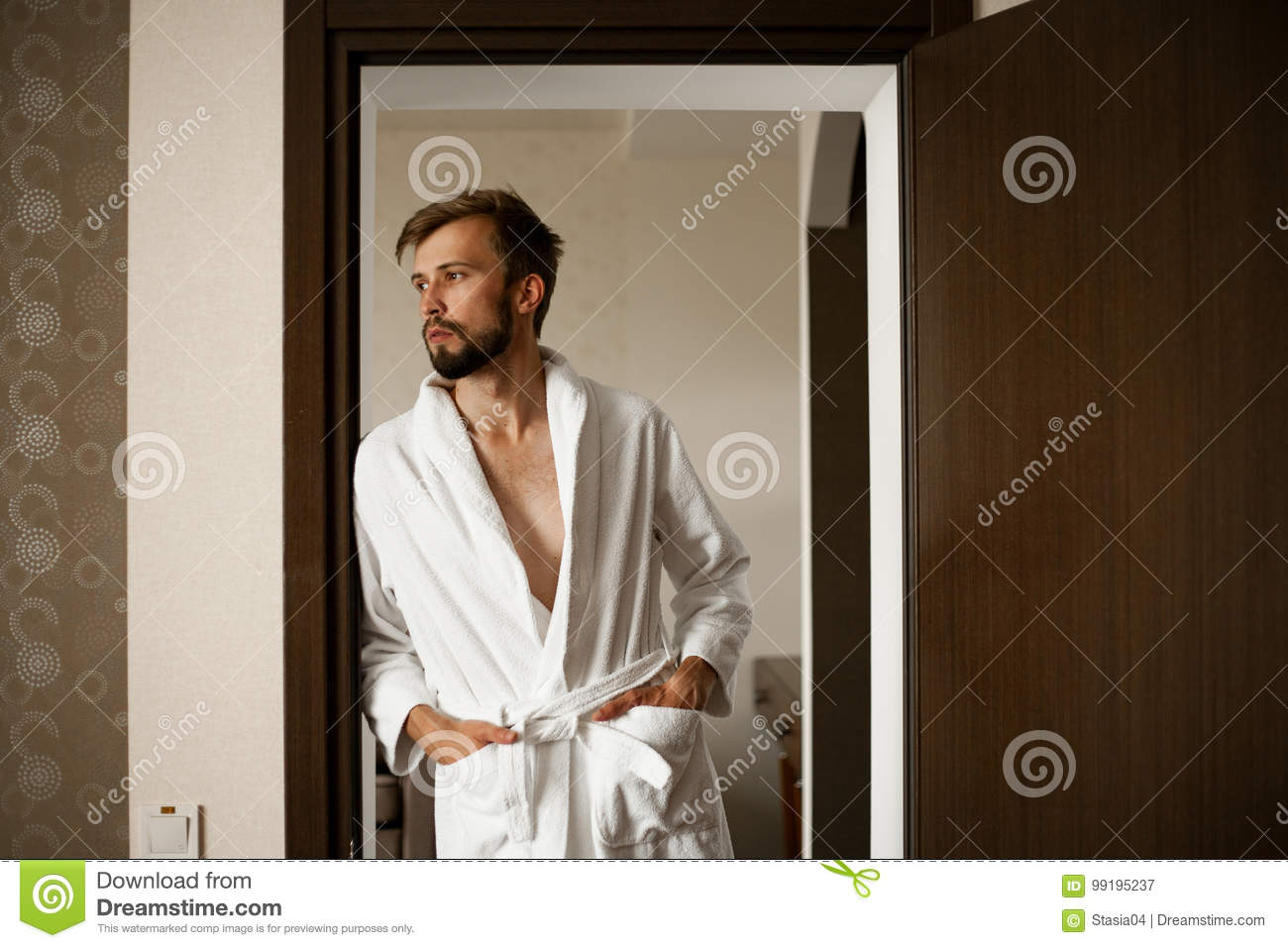 Young man stands in bathrobe and looks away.