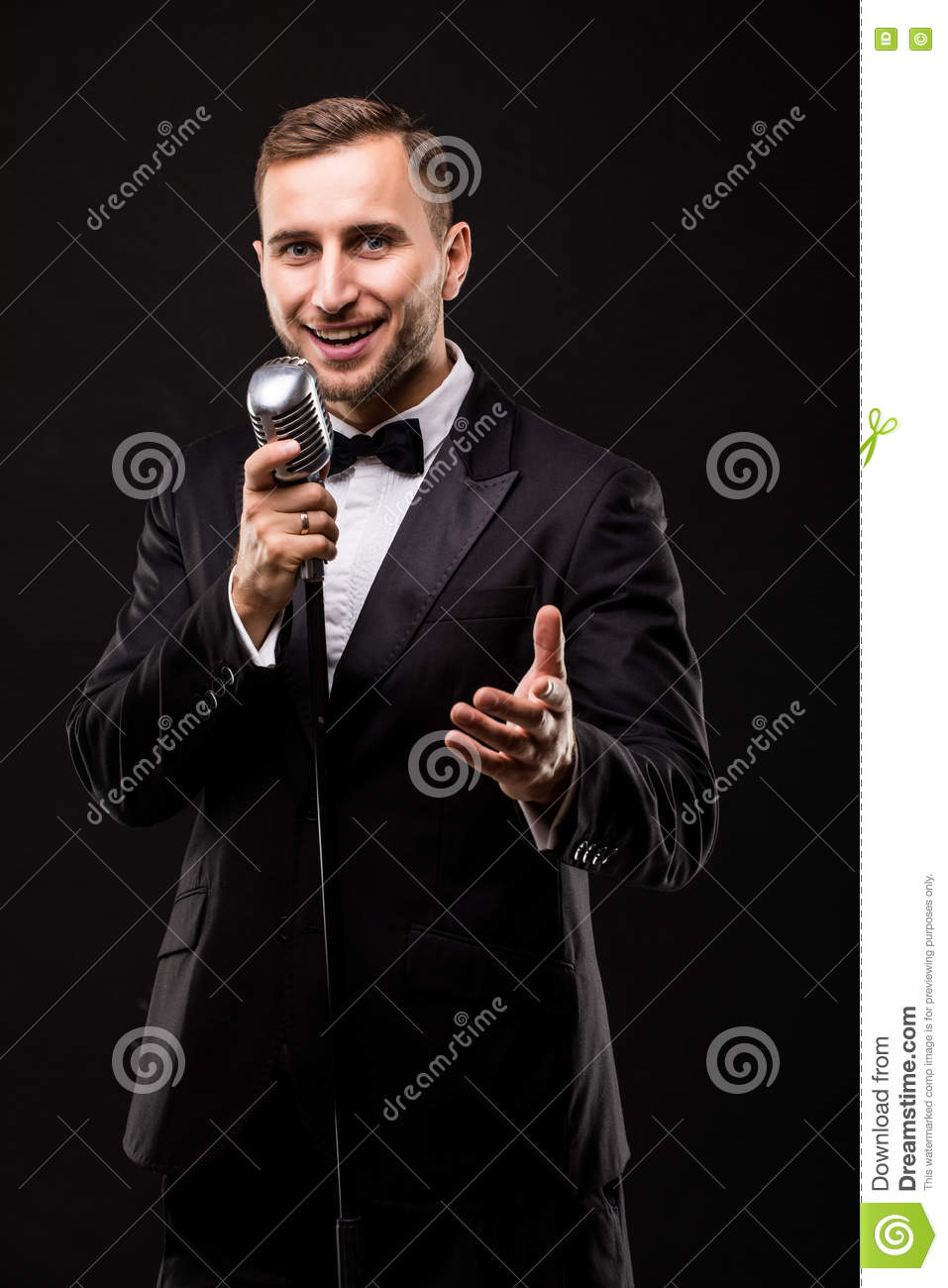 Young man in suit singing over the microphone with energy