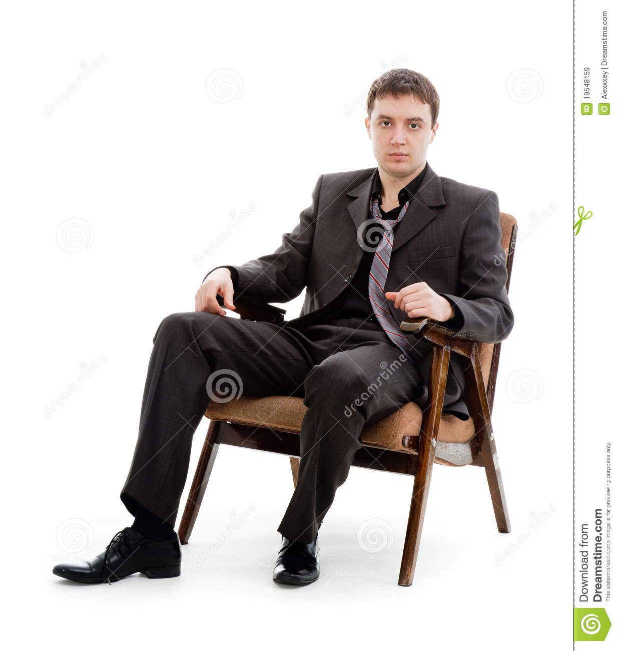 A young man in a suit and tie sitting in a chair stock for Sitting in armchair