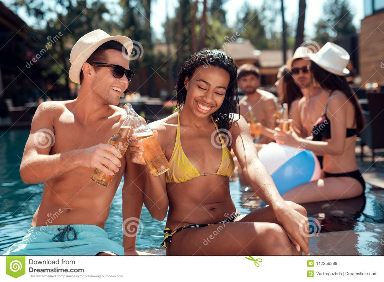 Young man is sunglasses and cheerful woman cheering with beer bottles in swimming pool.