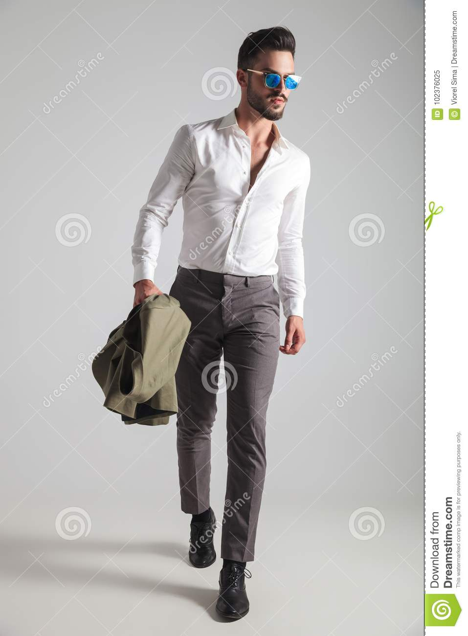 Young man in sunglasses looks to side while walking