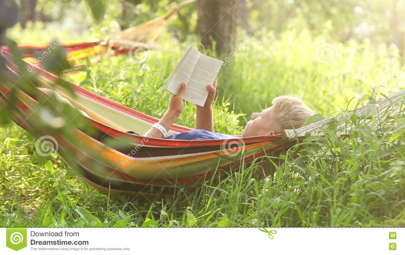 Young Man Sways Lying In The Hammock And Reads A Book During Siesta Stock  Footage   Video Of Idyllic, Living: 79974434