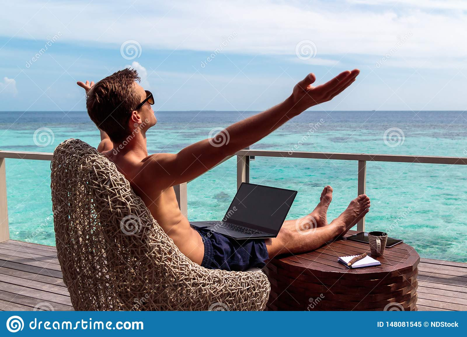 Young man in swimsuit working on a laptop in a tropical destination. arms raised, freedom concept