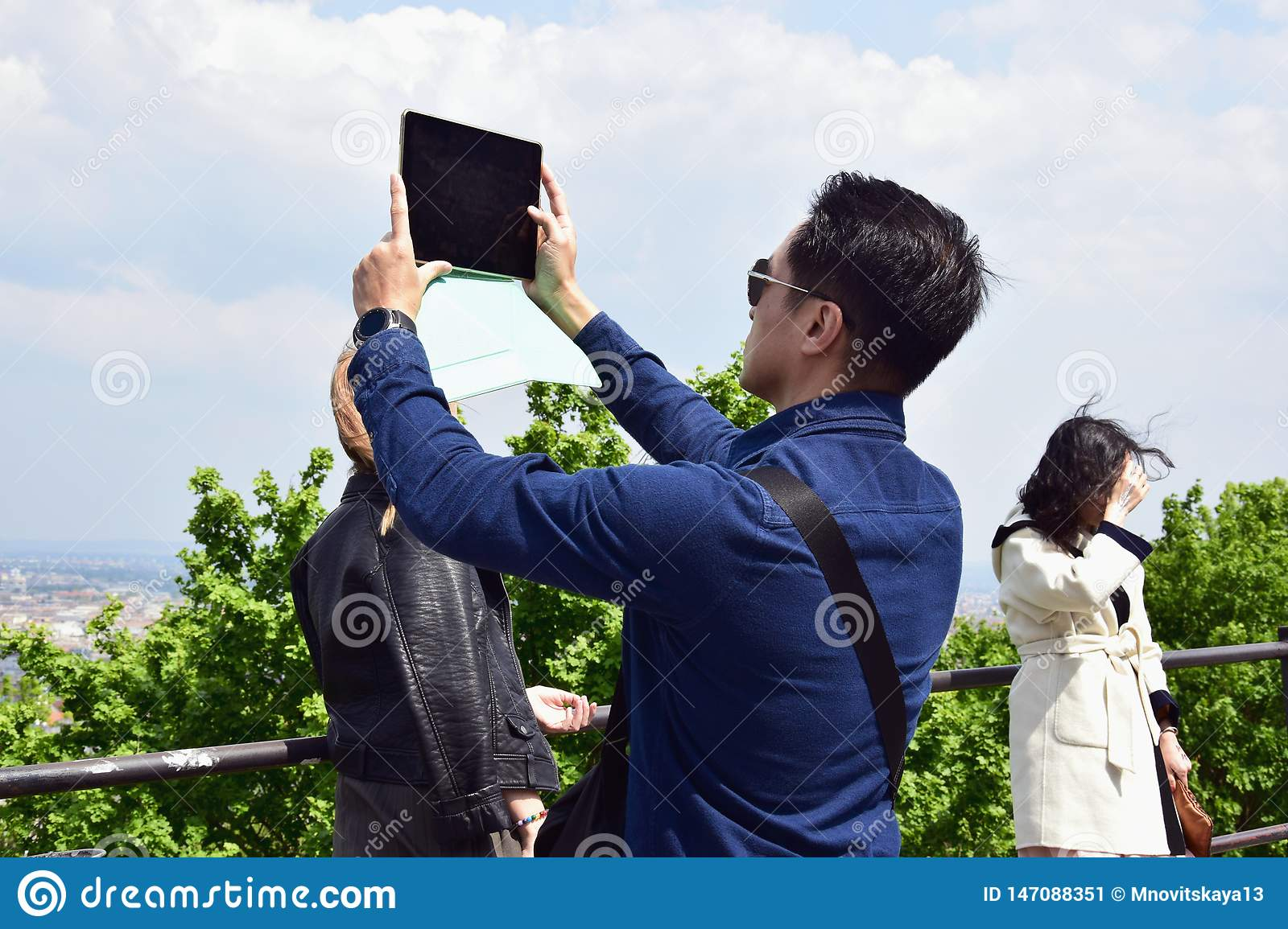 Young man takes a picture with a tablet of a picturesque view of the city