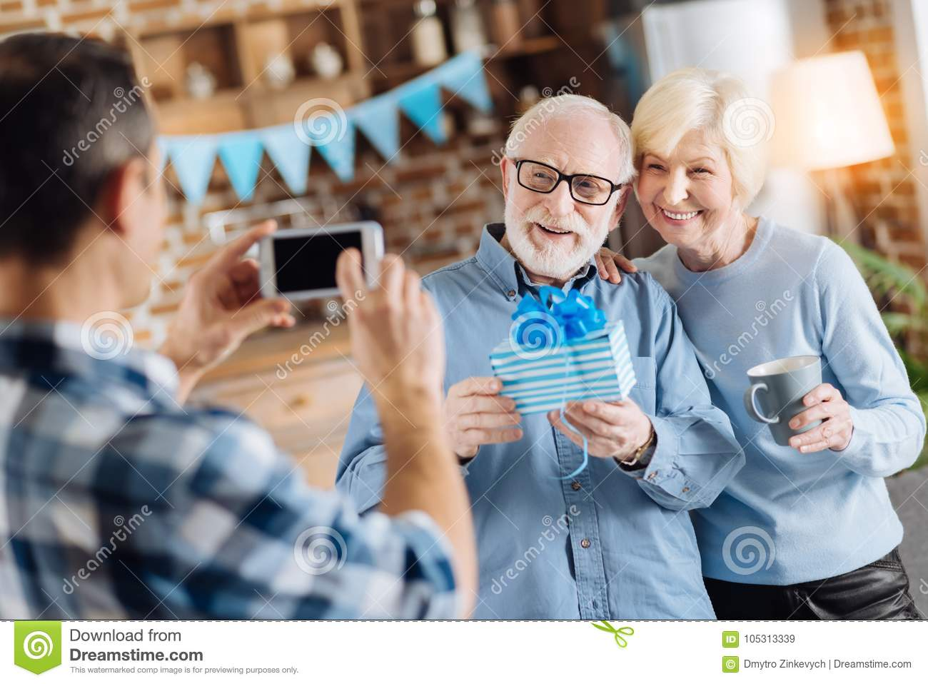 Loving Young Son Taking A Picture Of His Elderly Parents Posing With Birthday Present During The Party