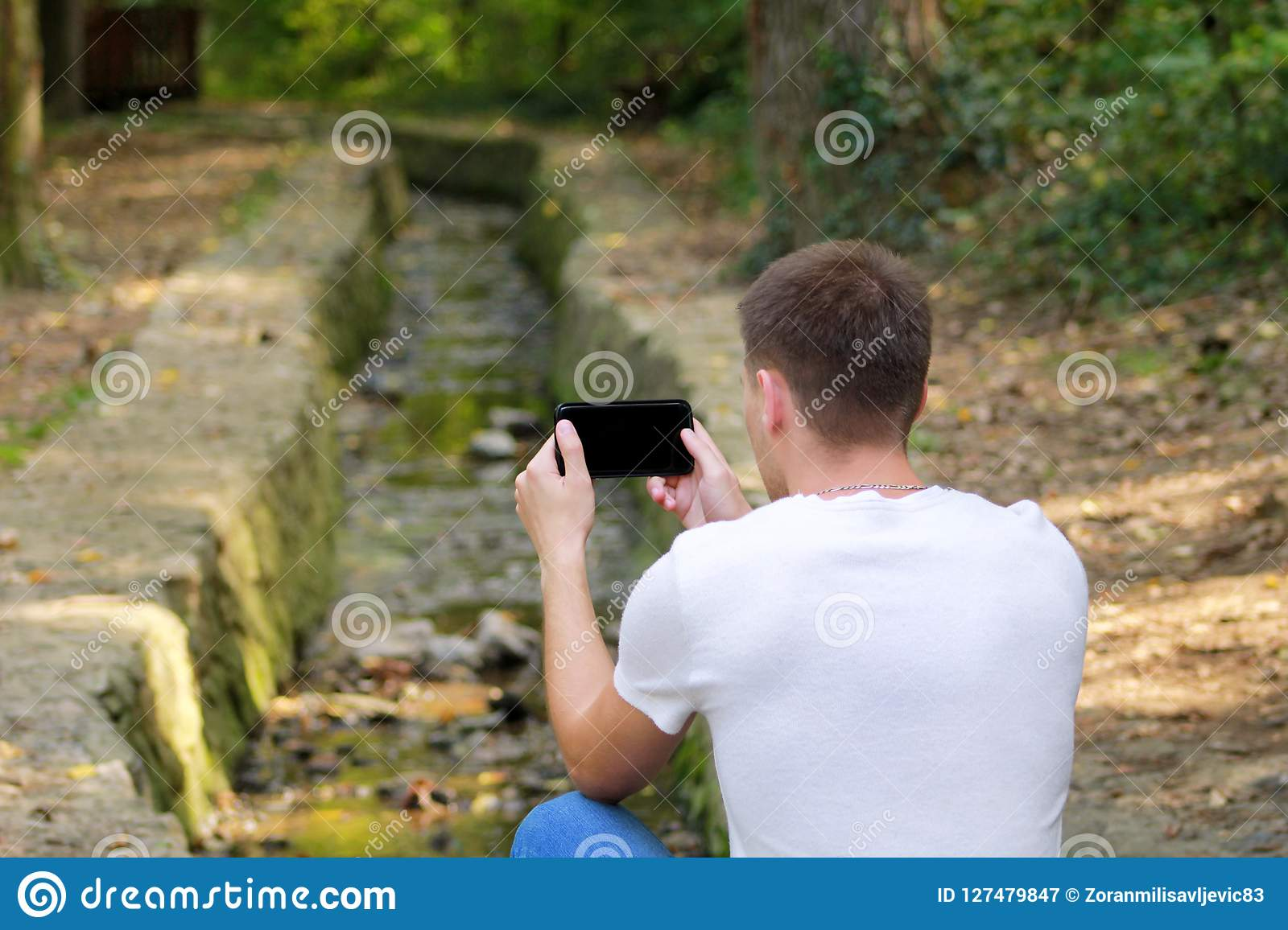 Young man taking pictures using camera his smart phone in nature, park and forest, a small river, a stream.