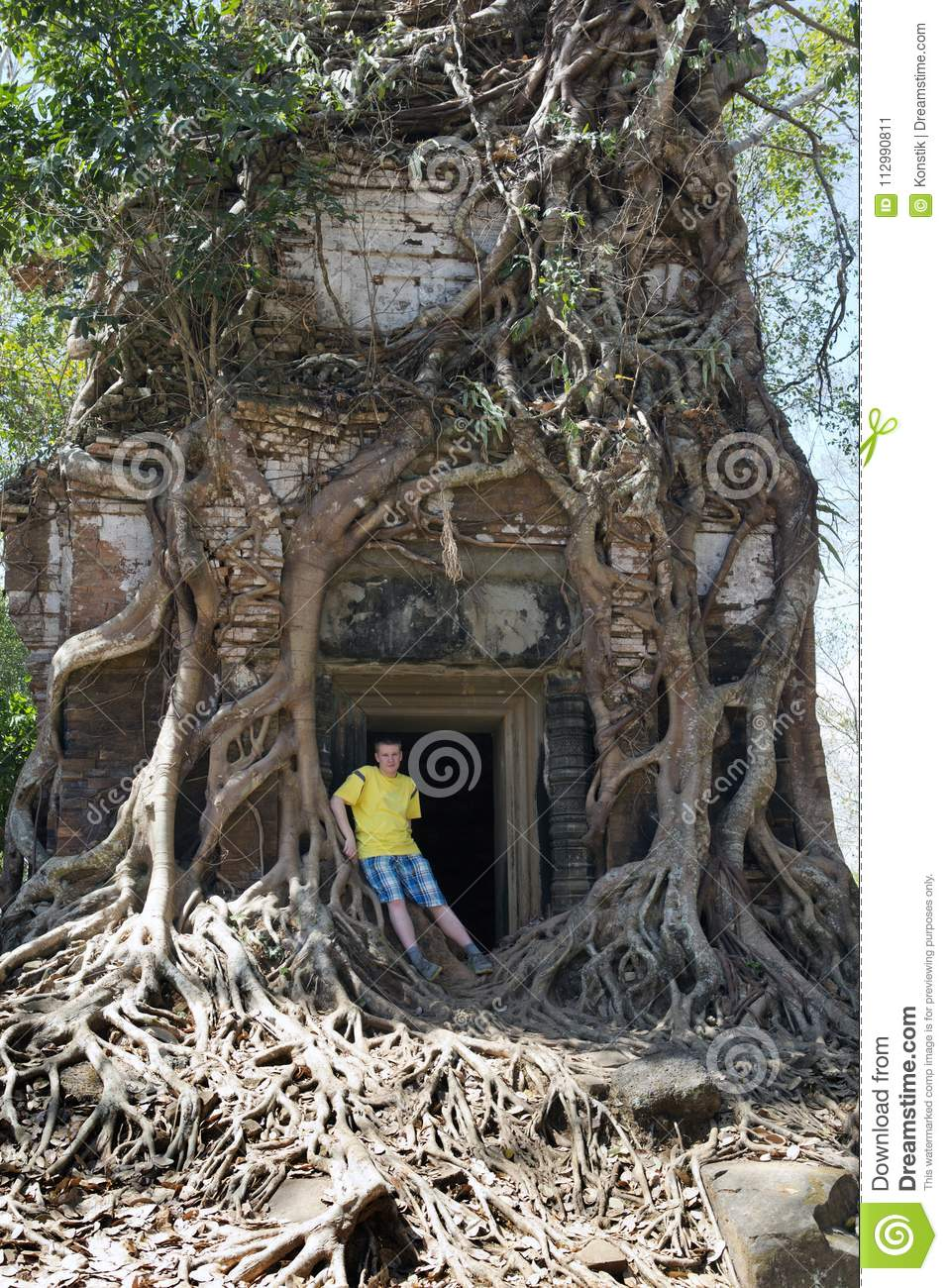 young man, the teenager at an entrance to the destroyed covered with roots of trees temple Prasat Chrap in the Koh Ker temple com