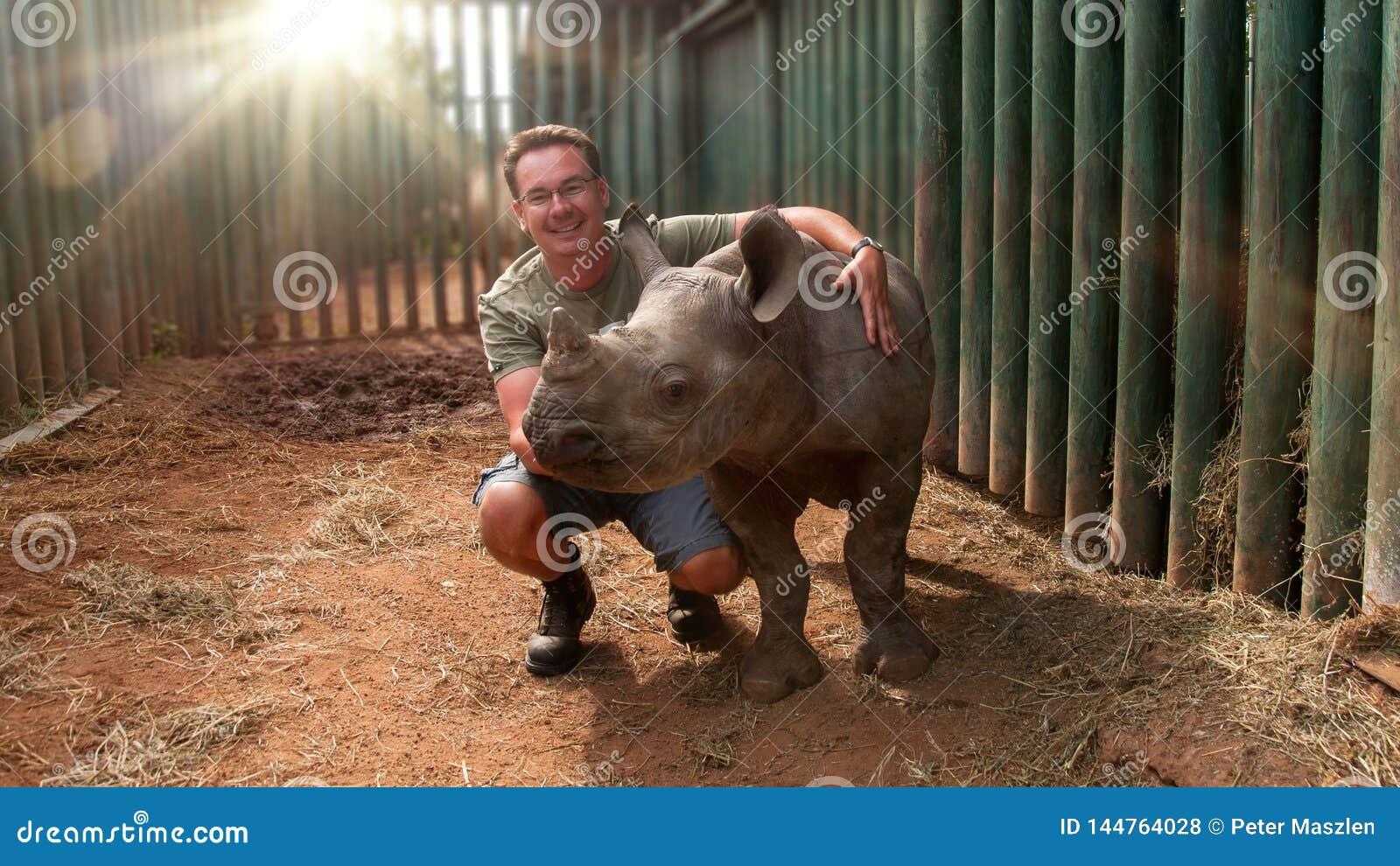 Young man touching rhinoceros baby