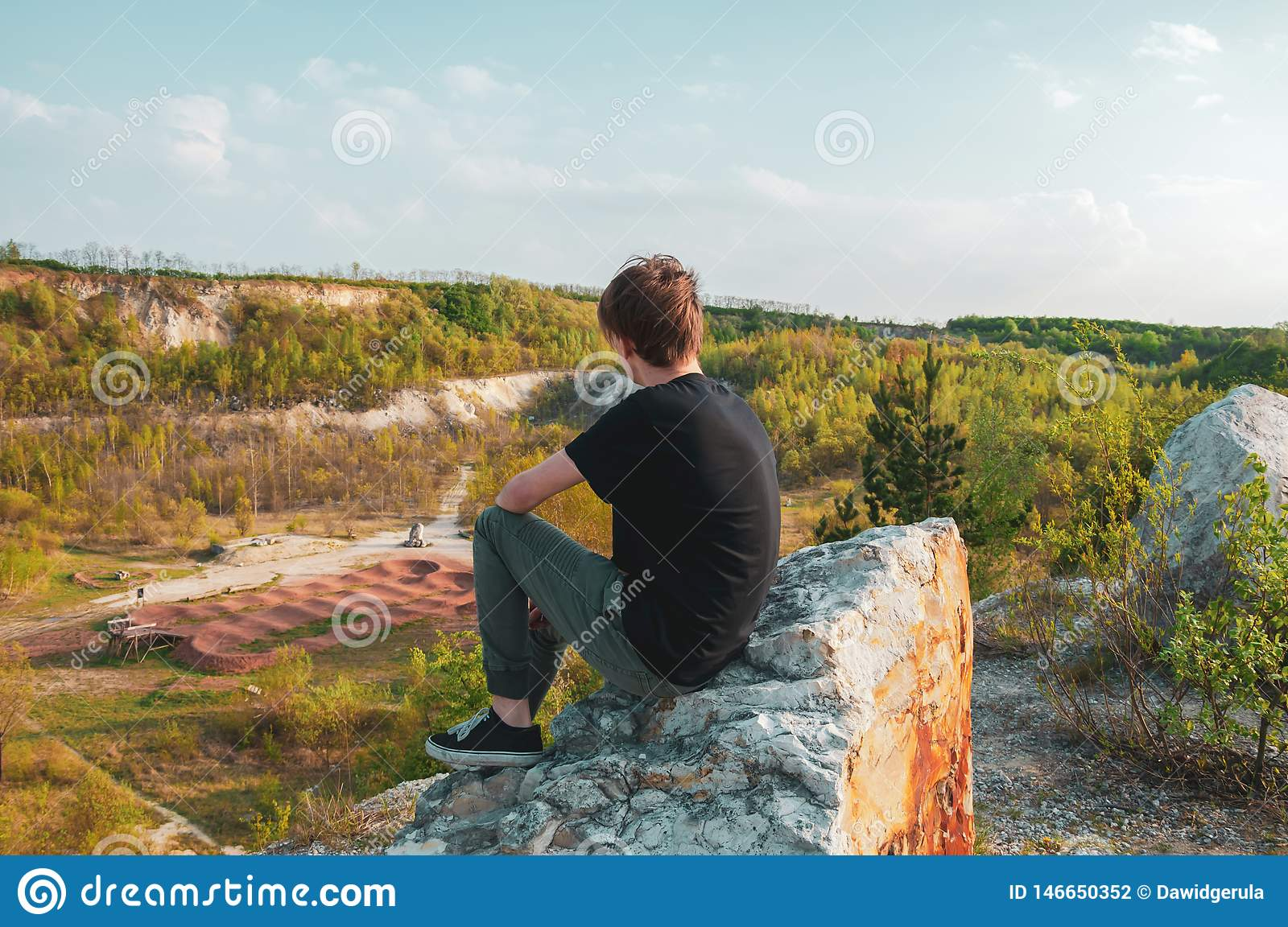 Young man tourist sitting on the giant rock, on the top of the mountain