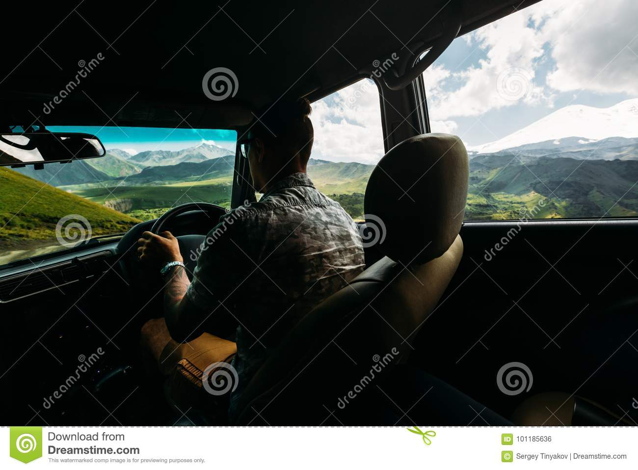 Young Man Traveler Driving A Car In The Mountains In Summer, Rear View From The Car