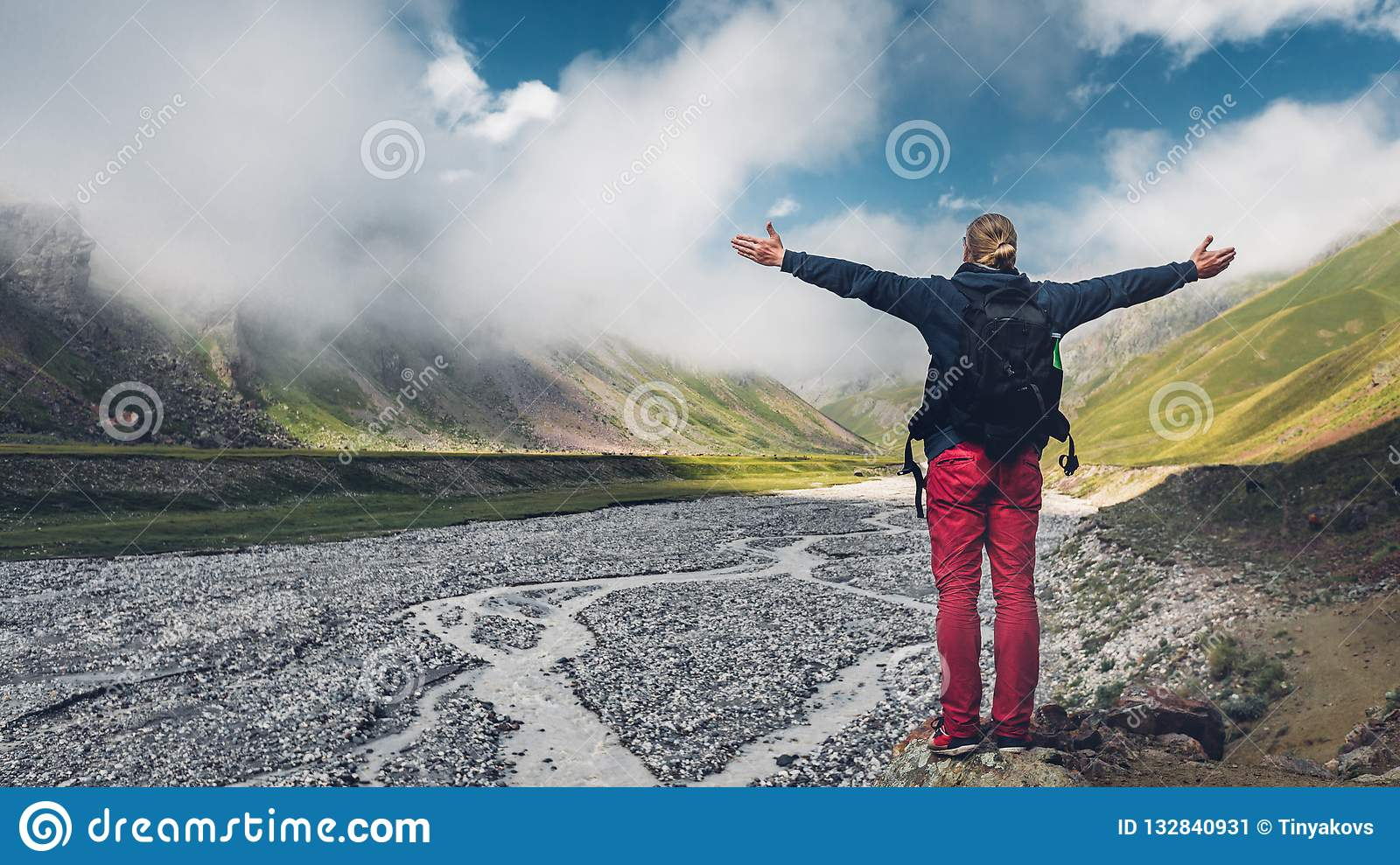 Young man traveler walking and enjoys view of summer spring mountains, rear view with copy-space. Concept of achieving motivation
