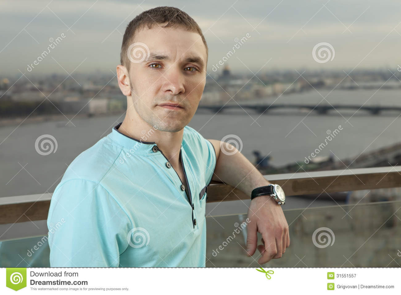 A young man in a turquoise shirt, short sleeve, portrait against the background of a European city. One person, a male, short hair