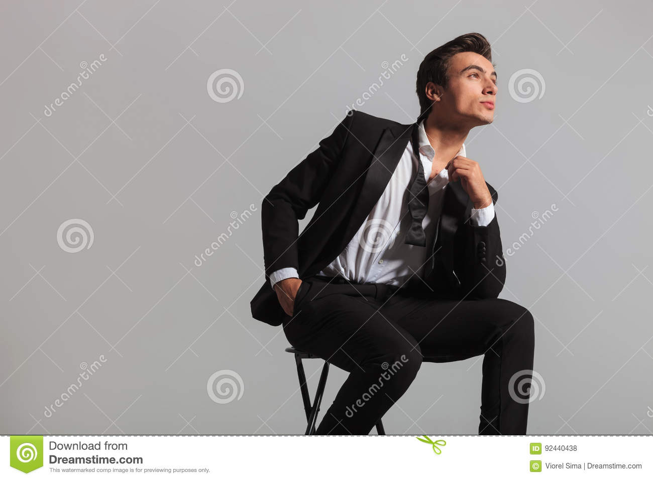 c47279e9c3b6 Young man in tuxedo and undone bowtie dreaming while sitting on chair in  studio