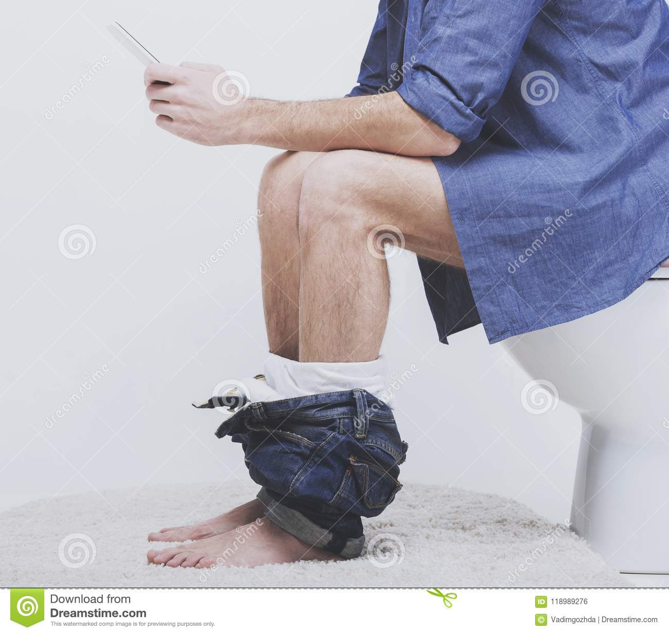 Young Man Sitting On Toilet Bowl At Bathroom Stock Photo