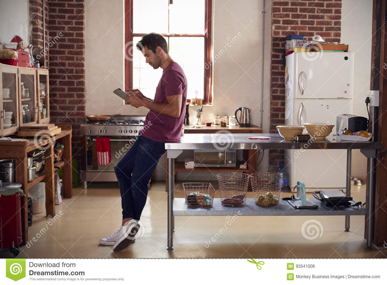 Young man using tablet computer in kitchen, full length