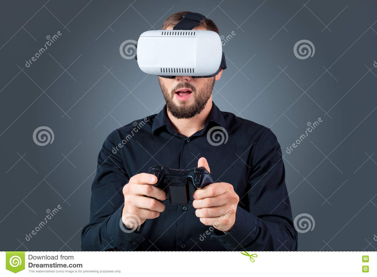 443839950d5c Excited young man using a VR headset glasses and experiencing virtual  reality on grey blue background. with a joystick in their hands
