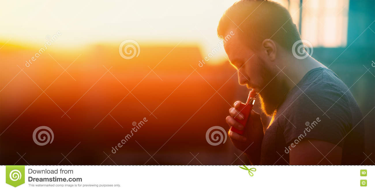 Young man with vaporiser tightening pairs on sunset sky background, blurred background, banner web site