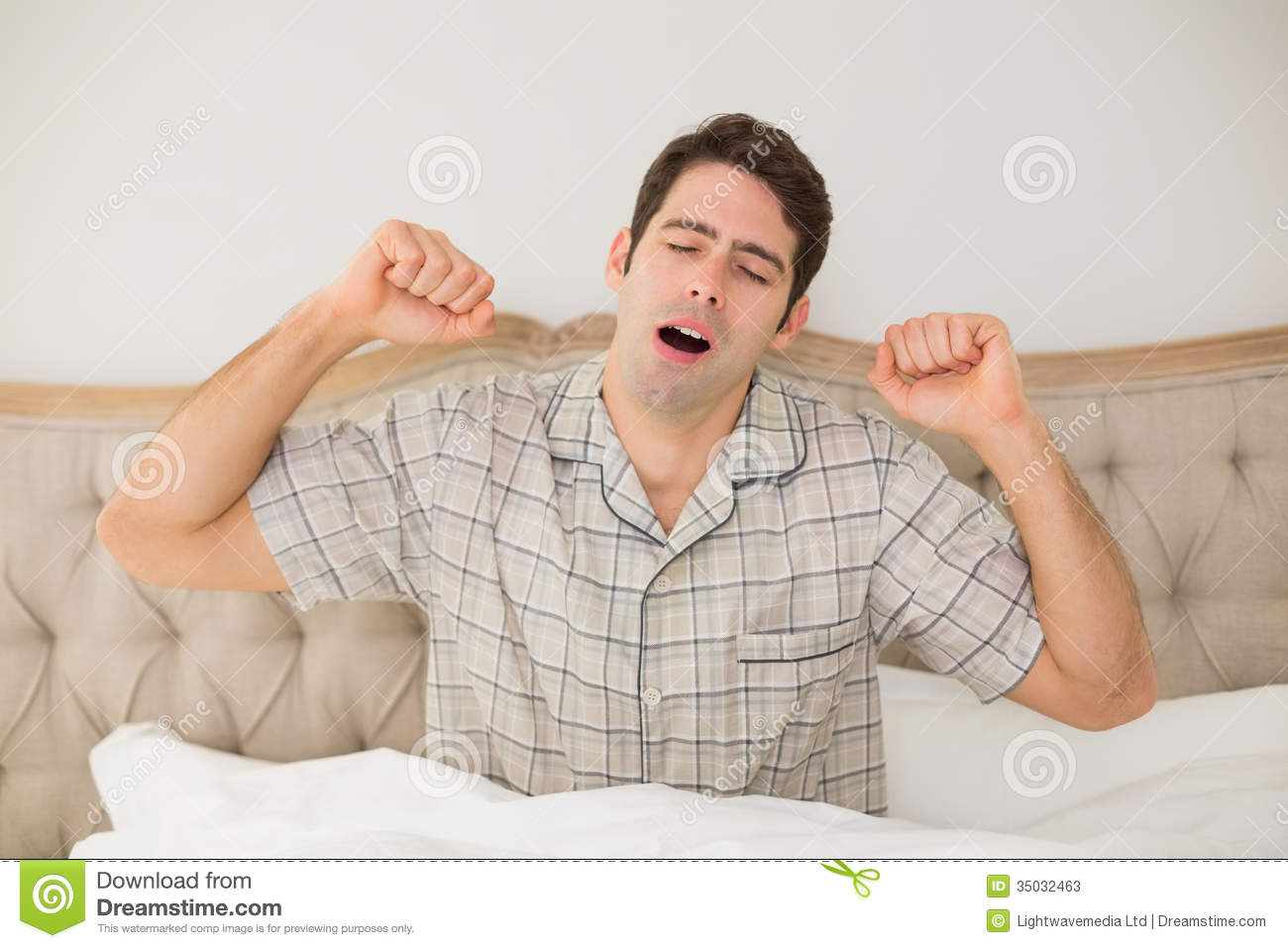 Young Man Waking Up In Bed And Stretching His Arms Stock Photos ...