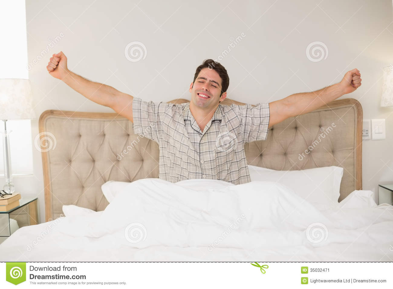 Young Man Waking Up In Bed And Stretching His Arms Stock