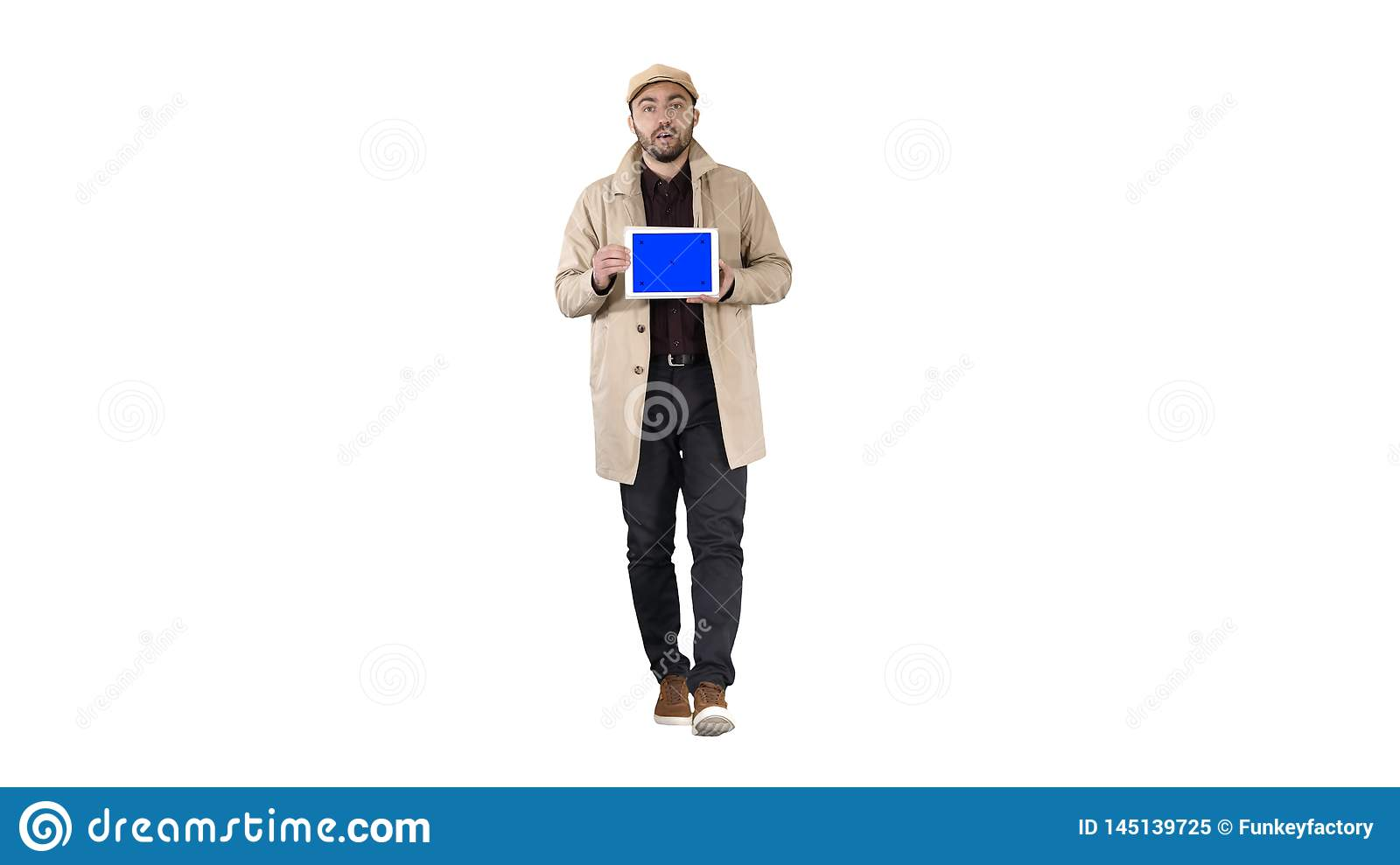Young man walking, talking and showing digital tablet with blue screen mockup on white background.