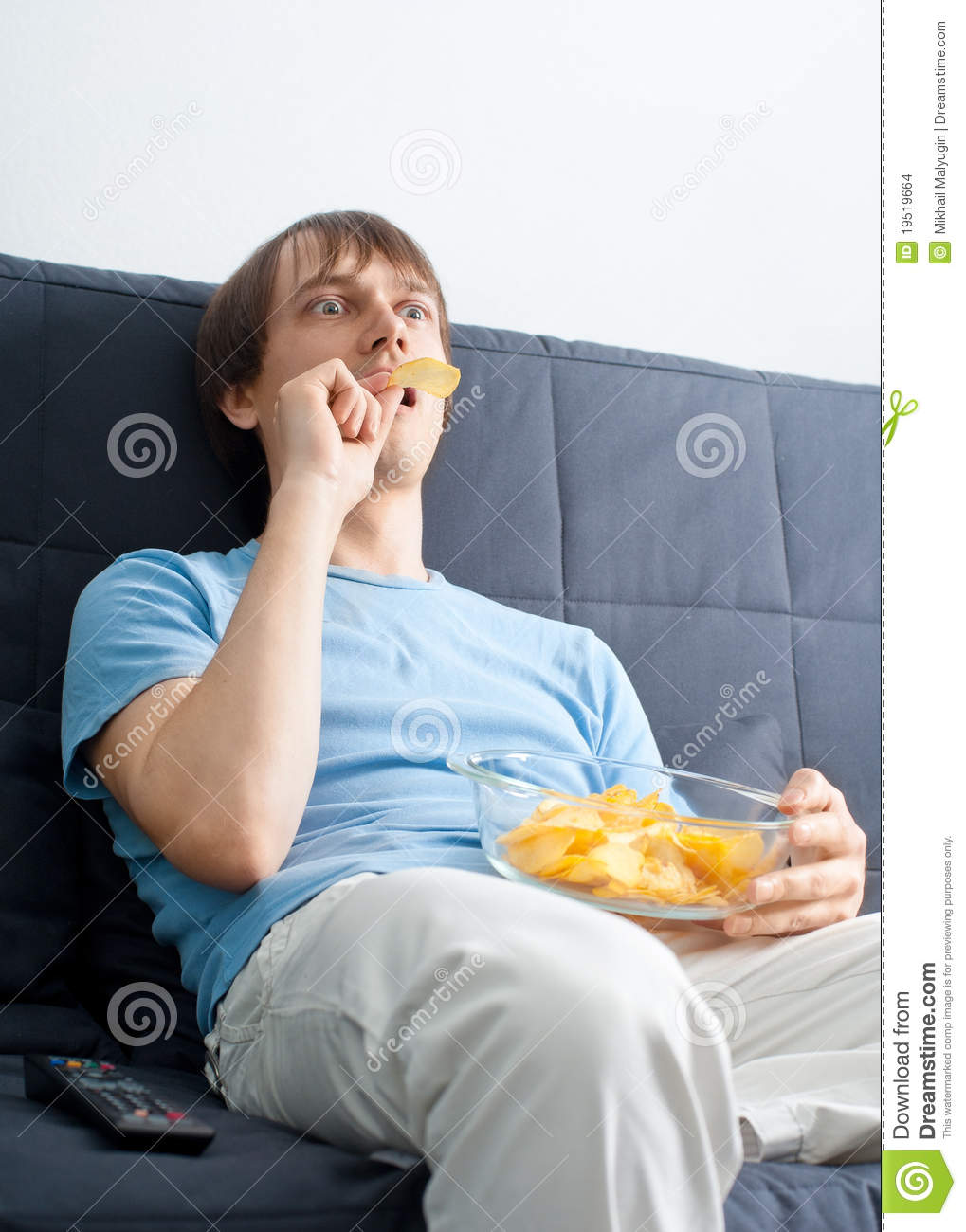 Young man watching tv and eating chips