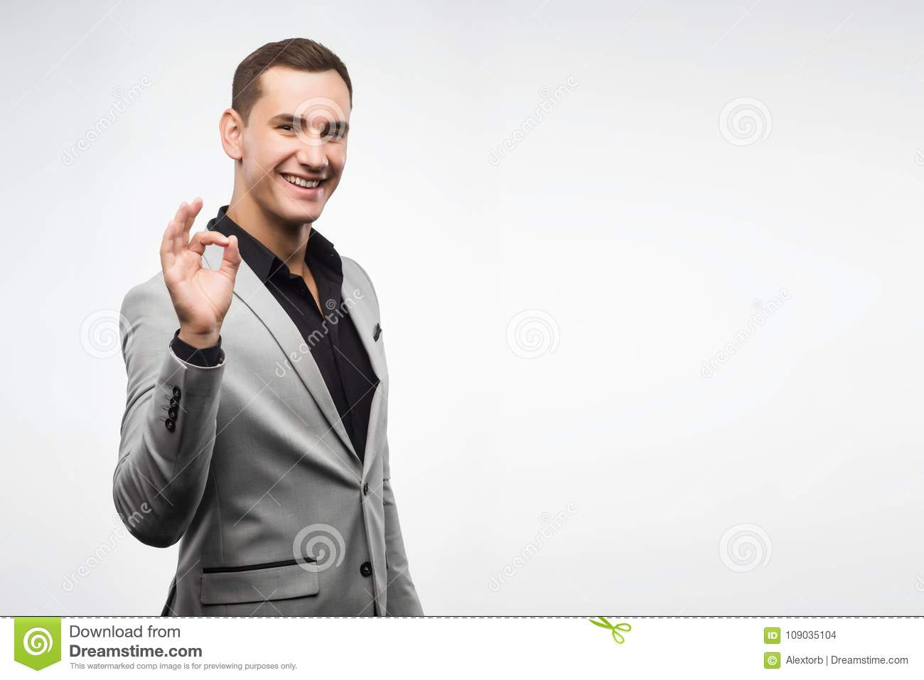 A young man wearing a gray suit shows a sign ok.