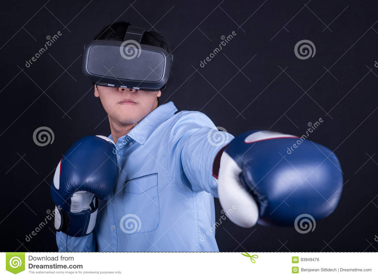 020fe573c469 Young asian man wearing virtual reality goggles with black background  studio in fighting pose. Smartphone using with VR headset.