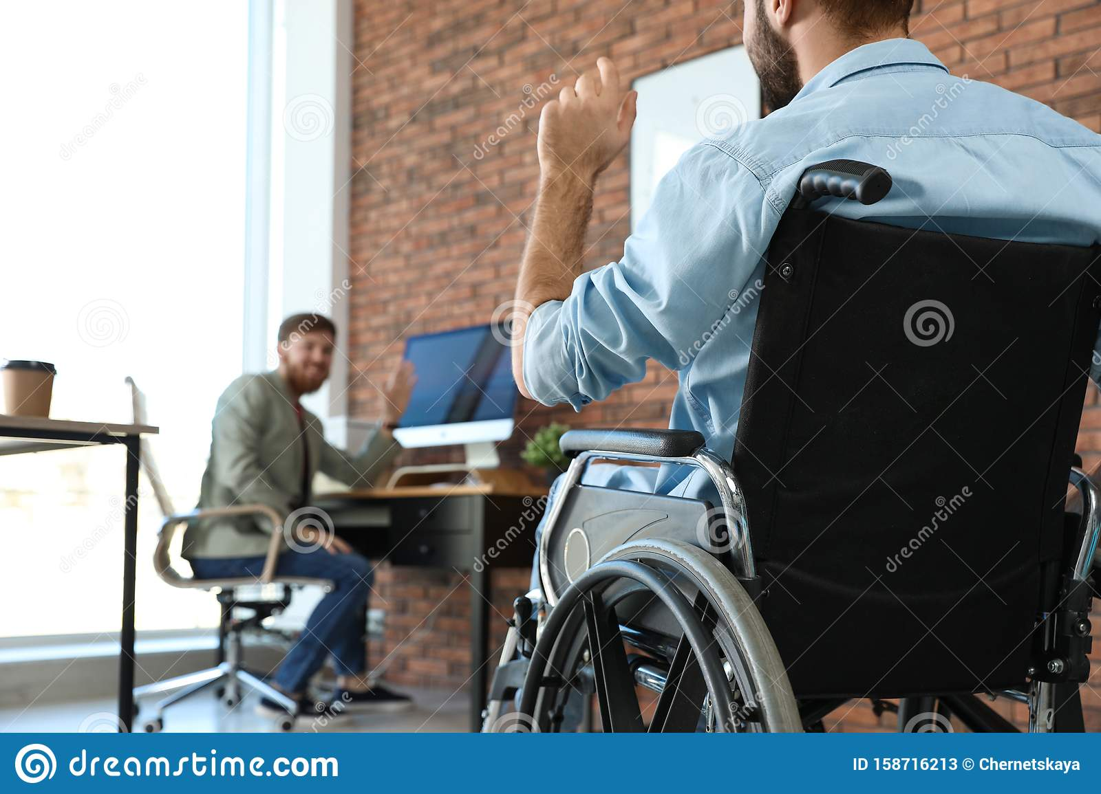 Young man in wheelchair with colleague at office