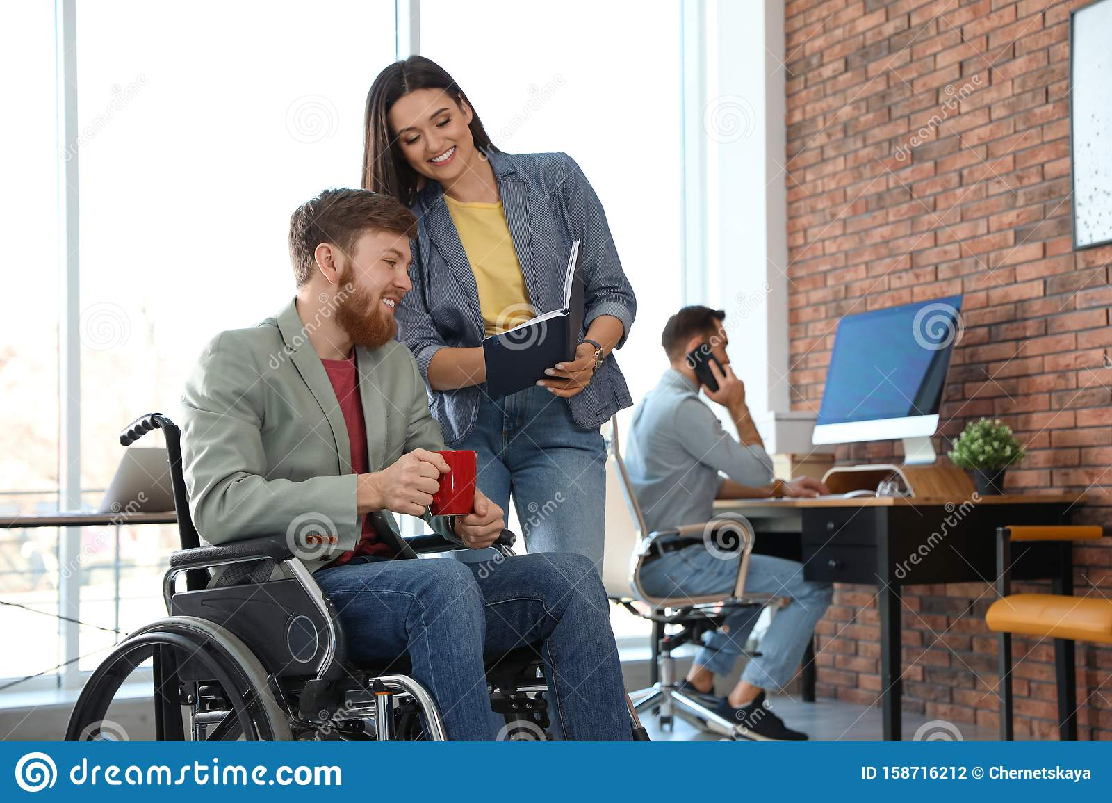 Young man in wheelchair with colleagues