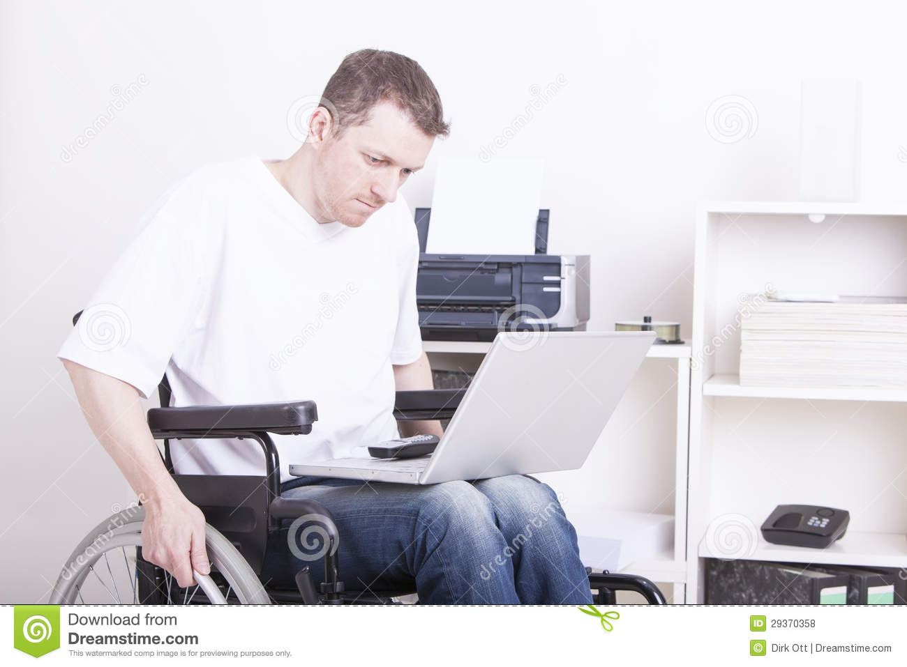 Young disabled man in wheelchair working in a home office using a