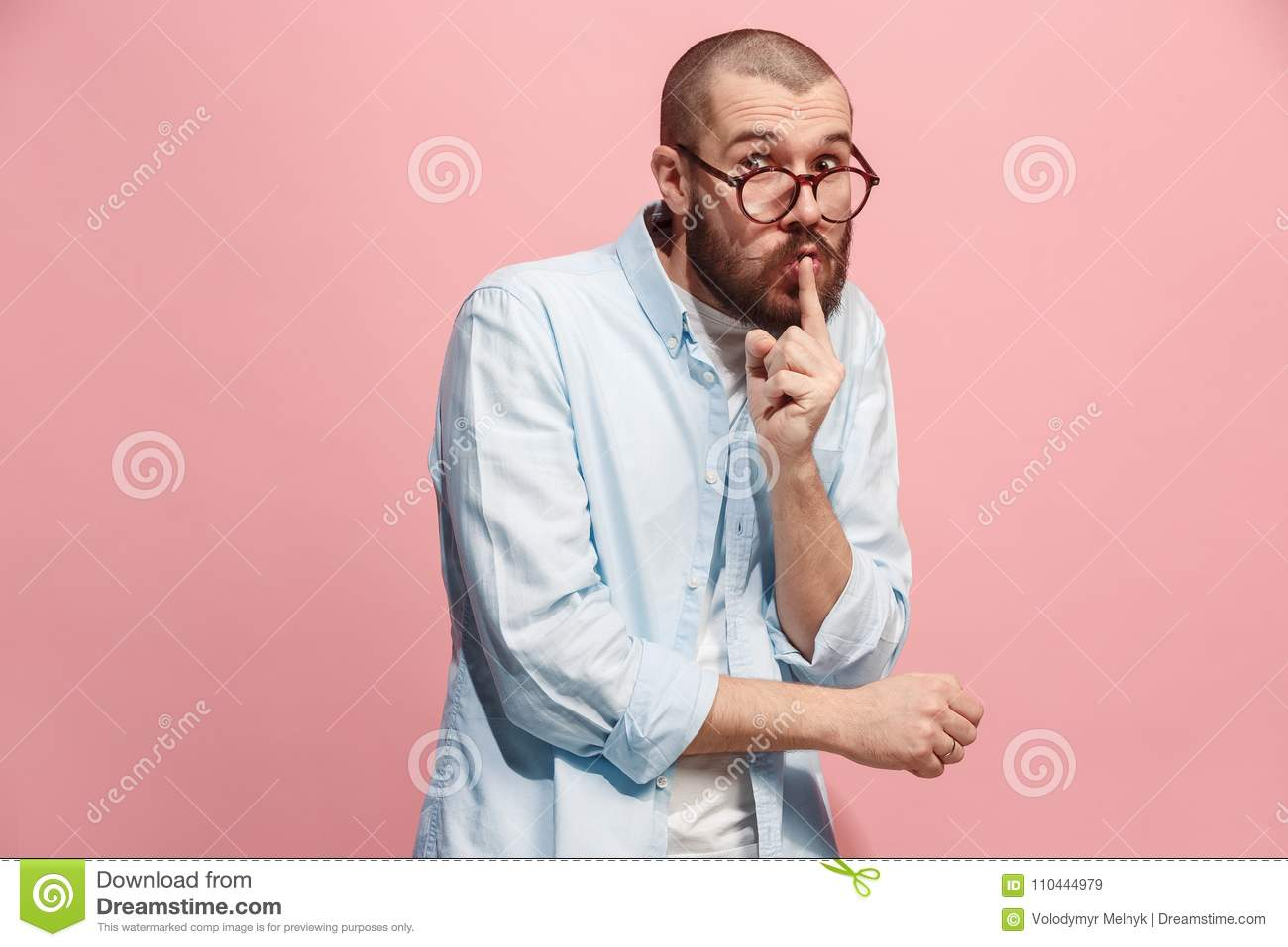 The young man whispering a secret behind her hand over pink background