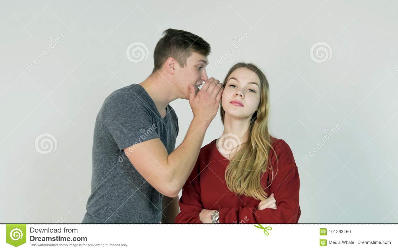 Young Man whispering a secret to a surprised young Woman. Young man tells a secret to the girl