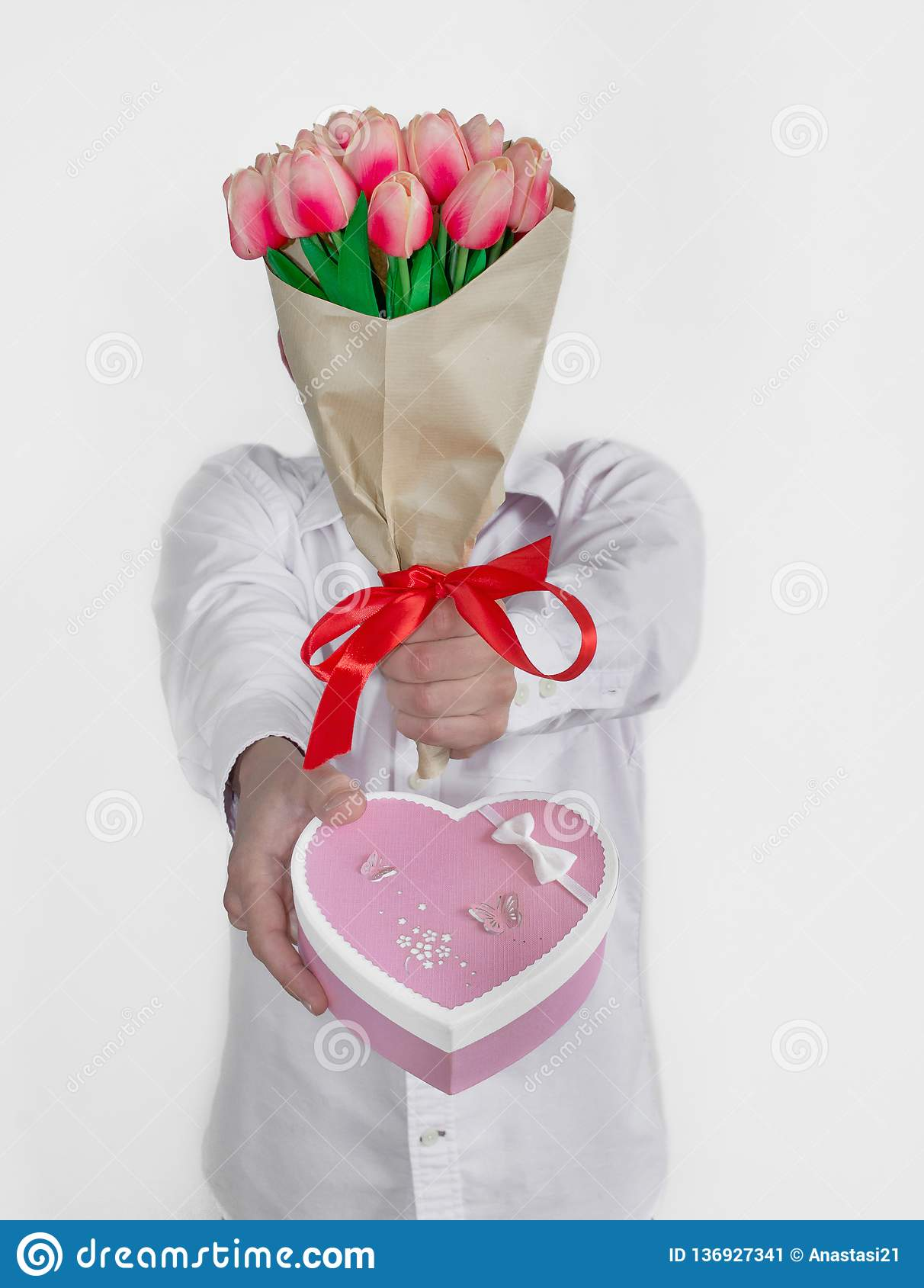 A young man in a white shirt and jeans holds a bouquet of tulips near his face and holds out a heart-shaped gift box
